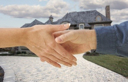 Man and woman shaking hands in front of a new house.